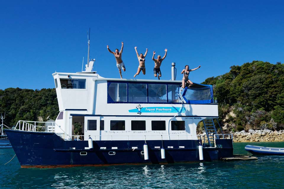 Backpackers jumping into the Abel Tasman